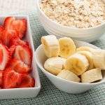 Fresh strawberry, banana, oat flakes in bowls. Breakfast. Selective focus. Rustic style.